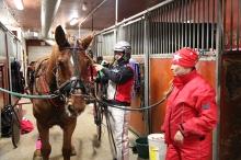 """Iikka Nurmonen ja Petra Honkanen varustavat Aki-Veitä vuoden viimeiseen lähtöön. """"Tarhasta sen on päästävä ensimmäisenä"""", Petra valottaa hevosen luonnetta."""